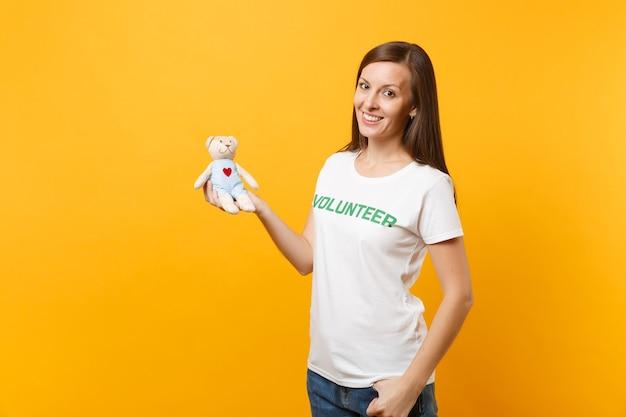 Retrato de mulher de camiseta branca com voluntário de título verde de inscrição escrita segurar ursinho de pelúcia brinquedo isolado em fundo amarelo. ajuda de assistência gratuita voluntária, conceito de trabalho de graça de caridade.