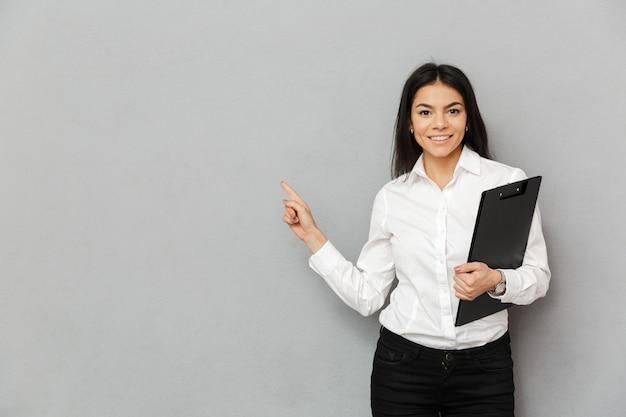 Retrato de mulher de escritório, com longos cabelos escuros, vestindo camisa branca, sorrindo e apontando o dedo de lado no espaço da cópia, segurando uma pasta com papéis, isolada sobre fundo cinza