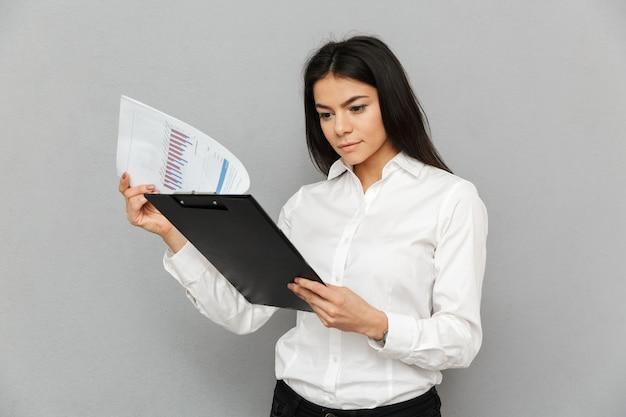 Retrato de mulher de escritório, com longos cabelos escuros, vestindo uma camisa branca, segurando uma pasta com papéis e lendo documentos, isolada sobre um fundo cinza
