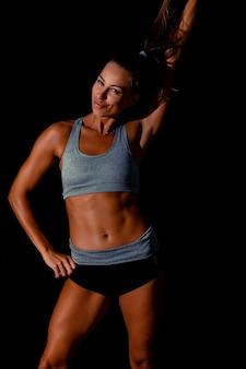 Retrato de mulher de esportes vestindo roupas esportivas pretas no escuro. sexy fit mulher posando em fundo preto.