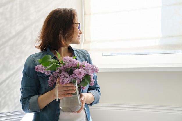 Retrato de mulher de meia idade com buquê de lilás