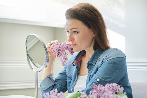 Retrato de mulher de meia idade com espelho de maquiagem