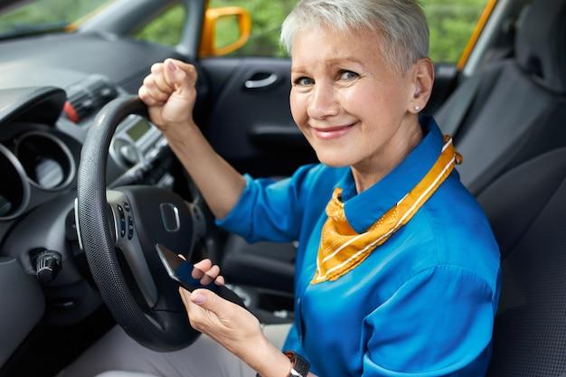Retrato de mulher de meia-idade estressada e infeliz com penteado de camisa sentado no banco do motorista, cerrando os punhos, segurando o telefone celular, ligando para o marido ou ligando para a assistência na estrada porque o carro está quebrado