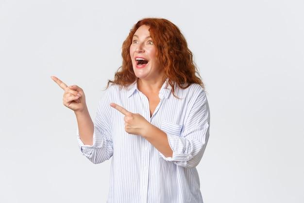 Retrato de mulher de meia-idade feliz e animada reage ao banner promocional emocionante, apontando e olhando o canto superior esquerdo fascinado, em pé otimista sobre um fundo branco.