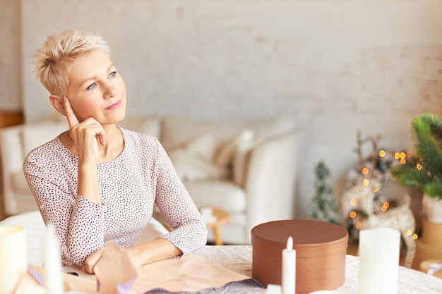 Retrato de mulher de meia-idade pensativa em um vestido elegante, sentada à mesa em uma sala decorada com guirlanda com aparência pensativa, segurando o dedo indicador na cabeça, pensando em como embrulhar presentes para a família