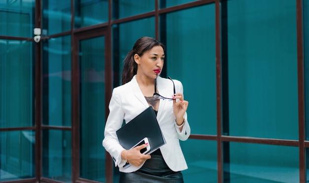 Retrato de mulher de negócios afro atenciosa com uma jaqueta branca
