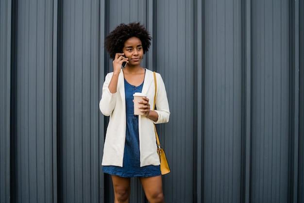 Retrato de mulher de negócios afro falando ao telefone e segurando uma xícara de café em pé ao ar livre na rua
