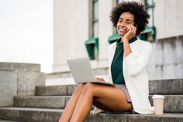 Retrato de mulher de negócios afro, falando no telefone e usando o laptop dela enquanto está sentado na escada ao ar livre. conceito de negócios. Foto Premium