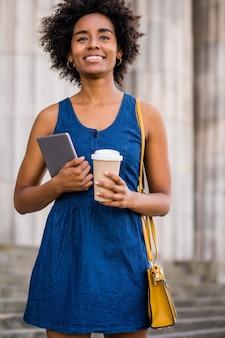 Retrato de mulher de negócios afro segurando um tablet digital e uma xícara de café em pé ao ar livre na rua. negócios e conceito urbano.