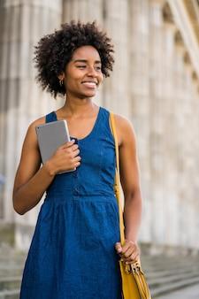 Retrato de mulher de negócios afro segurando um tablet digital em pé ao ar livre na rua. negócios e conceito urbano.