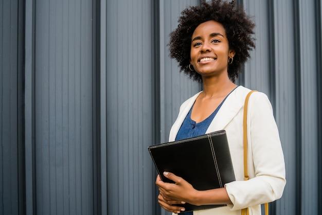 Retrato de mulher de negócios afro segurando uma prancheta enquanto caminha ao ar livre na rua