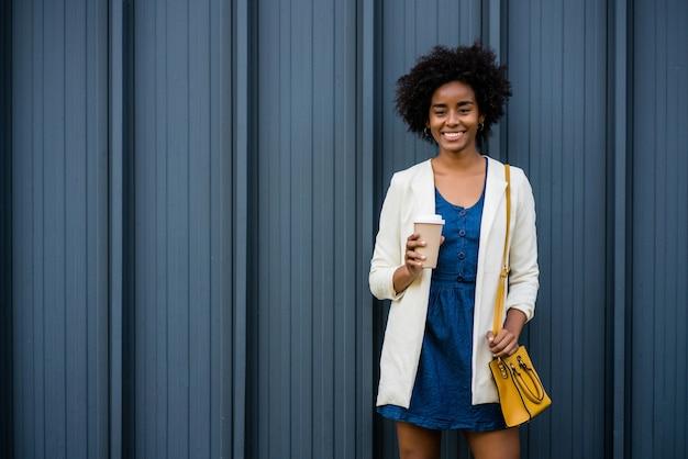 Retrato de mulher de negócios afro, segurando uma xícara de café em pé ao ar livre na rua. negócios e conceito urbano.