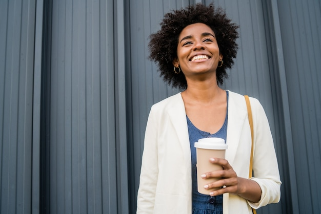 Retrato de mulher de negócios afro segurando uma xícara de café em pé ao ar livre na rua