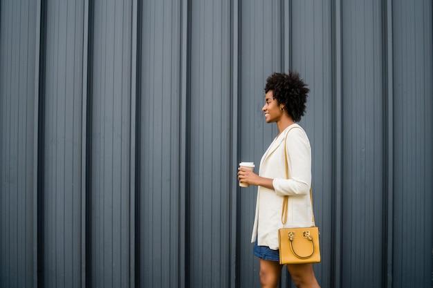 Retrato de mulher de negócios afro, segurando uma xícara de café enquanto caminha ao ar livre na rua. negócios e conceito urbano.
