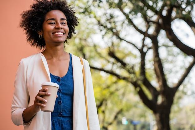 Retrato de mulher de negócios afro, sorrindo e segurando uma xícara de café em pé ao ar livre na rua. negócios e conceito urbano.