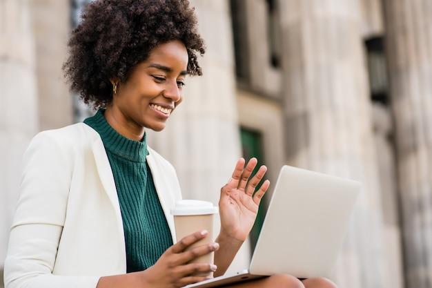 Retrato de mulher de negócios afro, tendo uma videochamada no laptop enquanto está sentado na escada ao ar livre. conceito urbano e empresarial.