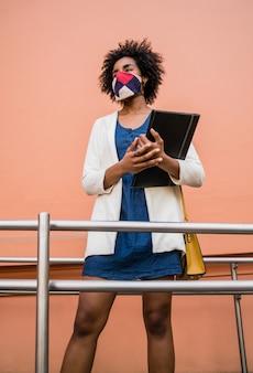 Retrato de mulher de negócios afro usando máscara protetora e segurando uma prancheta em pé ao ar livre na rua. conceito de negócios.