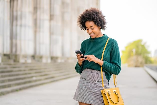 Retrato de mulher de negócios afro usando seu telefone celular em pé ao ar livre na rua. negócios e conceito urbano.