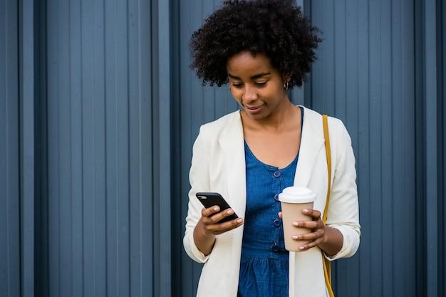 Retrato de mulher de negócios afro usando seu telefone celular em pé ao ar livre na rua.