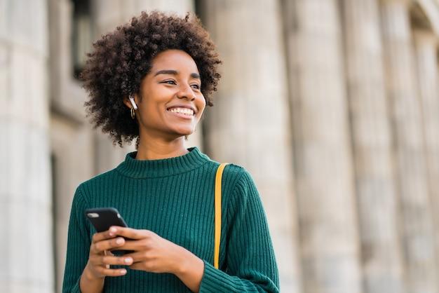 Retrato de mulher de negócios afro usando seu telefone celular em pé ao ar livre na rua