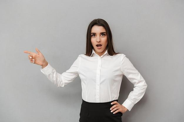 Retrato de mulher de negócios animada com cabelos castanhos compridos em camisa branca apontando o dedo de lado na copyspace com surpresa, isolado sobre uma parede cinza
