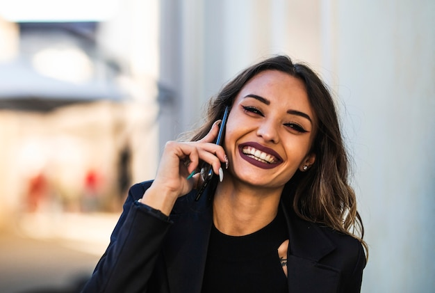 Retrato de mulher de negócios ao ar livre com o celular. close de menina morena