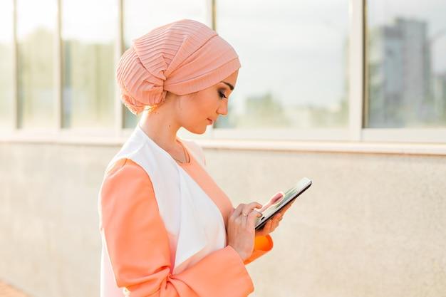 Retrato de mulher de negócios árabe segurando um tablet. a mulher está vestida com um abaya.