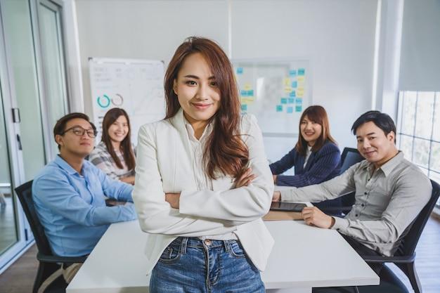 Retrato de mulher de negócios asiática com braços cruzados e em pé sobre o grupo de colegas