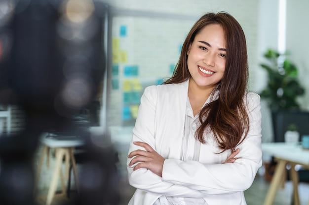 Retrato de mulher de negócios asiática com polegar para cima, como ao gravar um vídeo