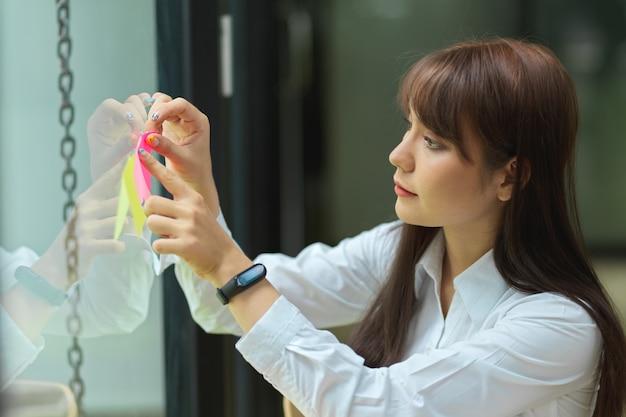 Retrato de mulher de negócios asiática compartilhando uma ideia de negócio em um post-it na janela de vidro