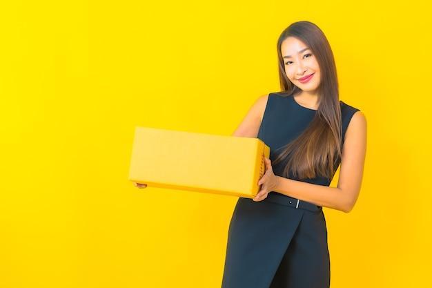 Retrato de mulher de negócios asiática jovem bonita com caixa marrom pronta para envio em fundo amarelo.