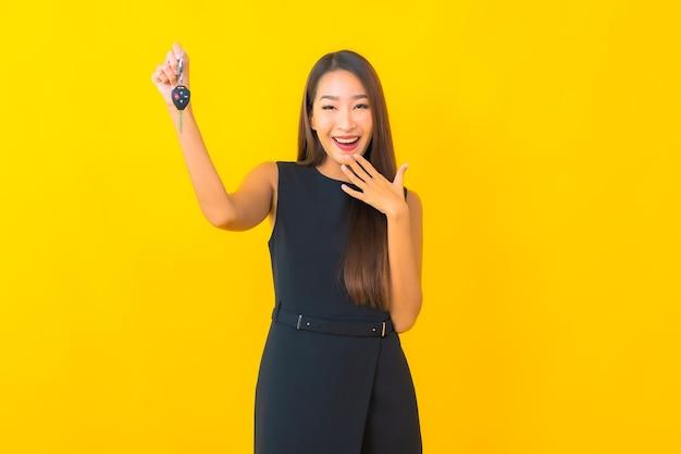 Retrato de mulher de negócios asiática jovem bonita com chave de carro em fundo amarelo.