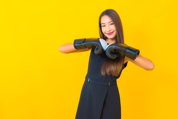 Retrato de mulher de negócios asiática jovem bonita com luva de boxe em fundo amarelo.