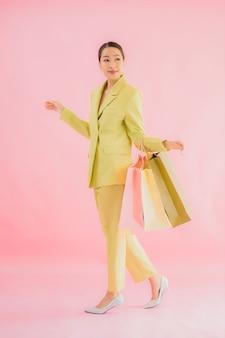 Retrato de mulher de negócios asiática jovem bonita com sacola de compras na cor isolada.