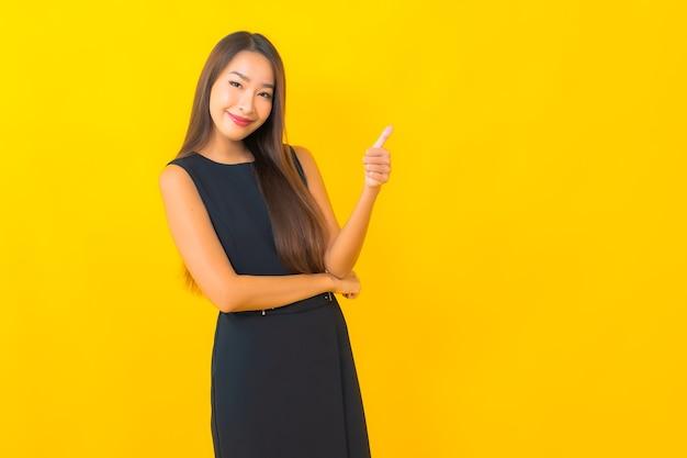 Retrato de mulher de negócios asiática jovem bonita sorrindo com ação sobre fundo de cor amarela.