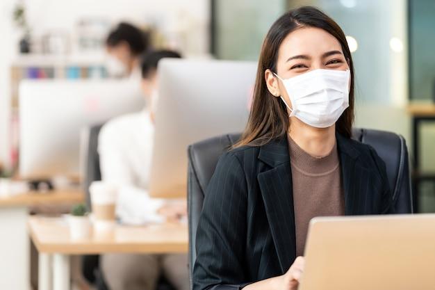 Retrato de mulher de negócios asiática usando máscara protetora no escritório