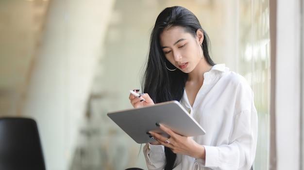 Retrato de mulher de negócios asiático bem sucedido usando tablet digital em pé no escritório moderno
