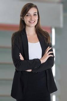 Retrato de mulher de negócios bonita com os braços cruzados no escritório cinza