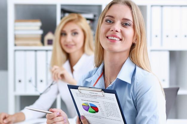 Retrato de mulher de negócios bonita. possui uma prancheta com estatísticas financeiras