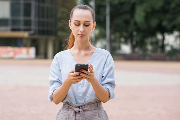 Retrato de mulher de negócios caucasiano atraente e bonita. lady está usando um smartphone. conceito de negócios e redes.