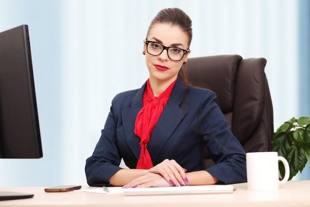 Retrato de mulher de negócios com laptop escreve em um documento em seu escritório