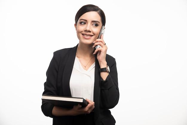 Retrato de mulher de negócios com notebook falando no telefone.