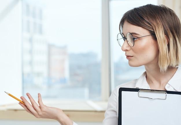 Retrato de mulher de negócios com uma folha de papel branca na pasta de finanças