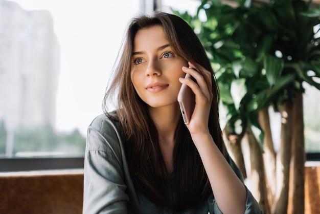 Retrato de mulher de negócios confiante segurando o celular, sentado no café