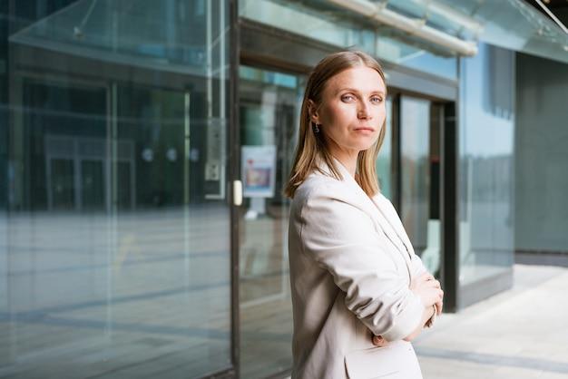 Retrato de mulher de negócios cruzou os braços feliz retrato profissional de sucesso perto de um prédio de escritórios.