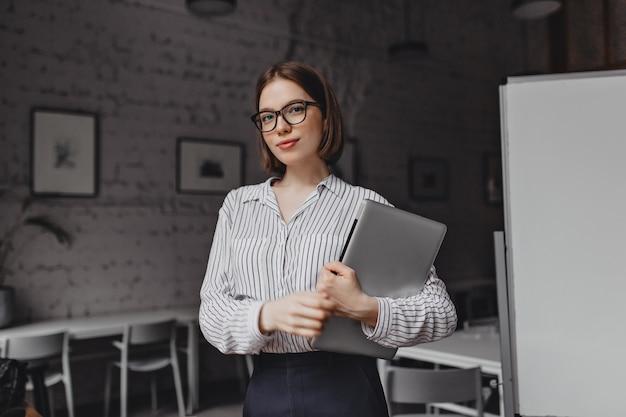 Retrato de mulher de negócios de olhos castanhos em roupa preto e branco e óculos elegantes, posando com o laptop na sala branca.