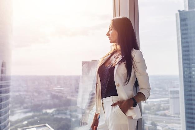 Retrato de mulher de negócios elegante, vestindo terno branco formal, em pé perto da janela, olhando a paisagem urbana.
