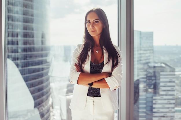 Retrato de mulher de negócios elegante, vestindo um terno branco formal, em pé perto da janela
