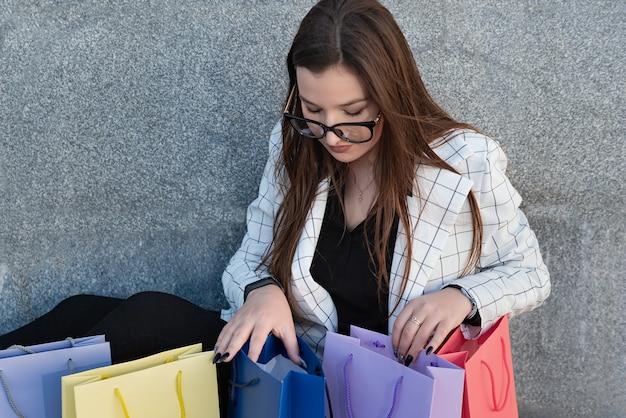 Retrato de mulher de negócios em jaqueta e óculos com sacolas multicoloridas.