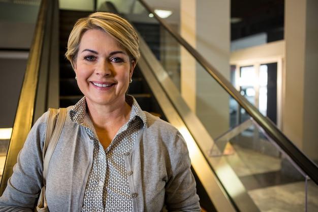 Retrato de mulher de negócios em pé na escada rolante